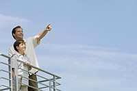 Man standing on balcony with son and pointing at sky