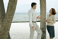 Man and woman standing next to tree trunk at the beach, smiling at each other