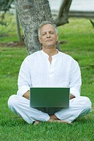 Mature man sitting in grass with laptop computer on lap, eyes closed