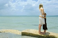 Mother and daughter standing by edge of sea, hugging, full length
