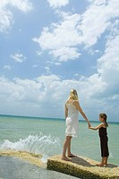 Mother and daughter standing by ocean as waves crash, holding hands and facing horizon, full length