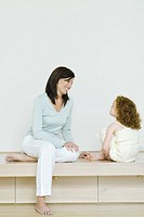 Woman and little girl sitting together, smiling at each other, full length