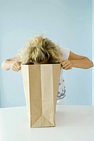 Woman leaning forward, looking into grocery bag
