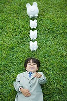 Boy dressed in suit lying on grass, laughing and pointing at camera, piggy banks above head