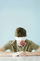 Teen boy wearing blindfold, smelling glass full of cherries