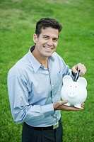 Man putting credit card into piggy bank