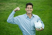 Man holding piggy bank, raising fist and smiling at camera