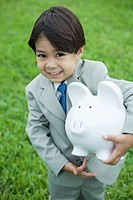 Little boy wearing full suit holding piggy bank under arm, smiling at camera