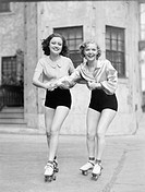 Two young women with roller blades skating on the road and smiling All persons depicted are not longer living and no estate exists Supplier warranties...