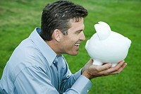 Man holding up piggy bank to face, smiling, side view