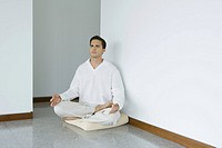 Man sitting in lotus position on cushion, looking away