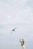 Man flying kite, looking up