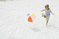 Young boy kicking beach ball at the beach, arms out