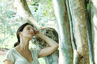 Woman leaning against tree trunk, head back, eyes closed