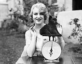 Portrait of a young woman weighing her puppy on a weighing scale All persons depicted are not longer living and no estate exists Supplier warranties t...