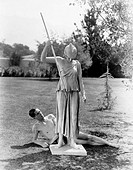 Nude man outside with statue of woman with spear All persons depicted are not longer living and no estate exists Supplier warranties that there will b...