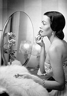 Young woman looking into a mirror and putting on make up All persons depicted are not longer living and no estate exists Supplier warranties that ther...