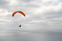 Person with parachute in sky