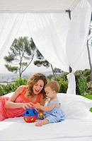 Woman and baby on bed outdoors