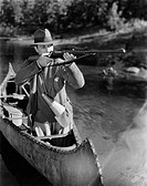 Man aiming gun from canoe All persons depicted are not longer living and no estate exists Supplier warranties that there will be no model release issu...
