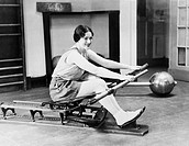 Woman using rowing machine All persons depicted are not longer living and no estate exists Supplier warranties that there will be no model release iss...