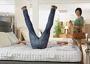 Man falling back onto bed in a store