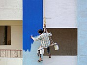 A Painter is seating on a cradle and working on a building's exterior painting work. Pune, Maharashtra, India