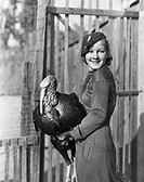Smiling woman holding live turkey All persons depicted are not longer living and no estate exists Supplier warranties that there will be no model rele...