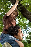 Young boy on shoulders of father grabs branches above, Assiniboine Park, Winnipeg, Canada