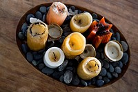 High angle view of candles and pebbles in a wooden tray