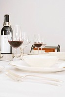 Wine bottle and wine glasses with tableware on a dining table