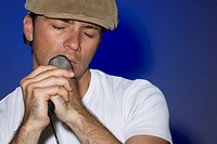 Close-up of a young man singing into a microphone