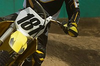 Mid section view of a motocross rider riding a motorcycle