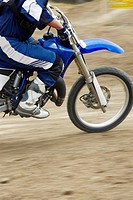 Low section view of a motocross rider riding a motorcycle