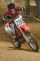 Motocross rider riding a motorcycle and leaning into a turn