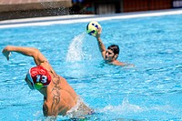 Mid adult man and a young man playing water polo in a swimming pool