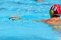 Rear view of a mid adult man playing water polo in a swimming pool