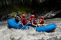 Side profile of five people rafting in a river