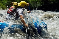 Side profile of two people rafting in a river