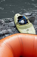 Close-up of an inflatable raft and a kayak at a riverbank