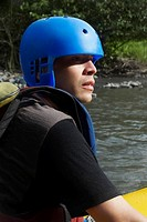 Side profile of a young man rafting in a river