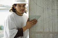 Portrait of a young man holding a set square