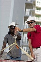Two male construction workers working at a construction site