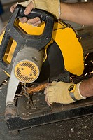 Close-up of a man's hands working on an electric saw