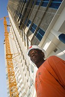 Low angle view of a male construction worker standing in front of a building
