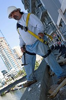 Mature man standing at the edge of a building and holding a hammer