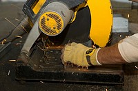 Close-up of a person's hands using an electric saw