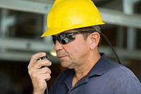 Close-up of a male construction worker talking on a CB radio