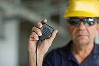 Close-up of a male construction worker holding a CB radio