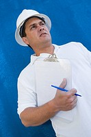 Low angle view of a male construction worker holding a clipboard and a pen